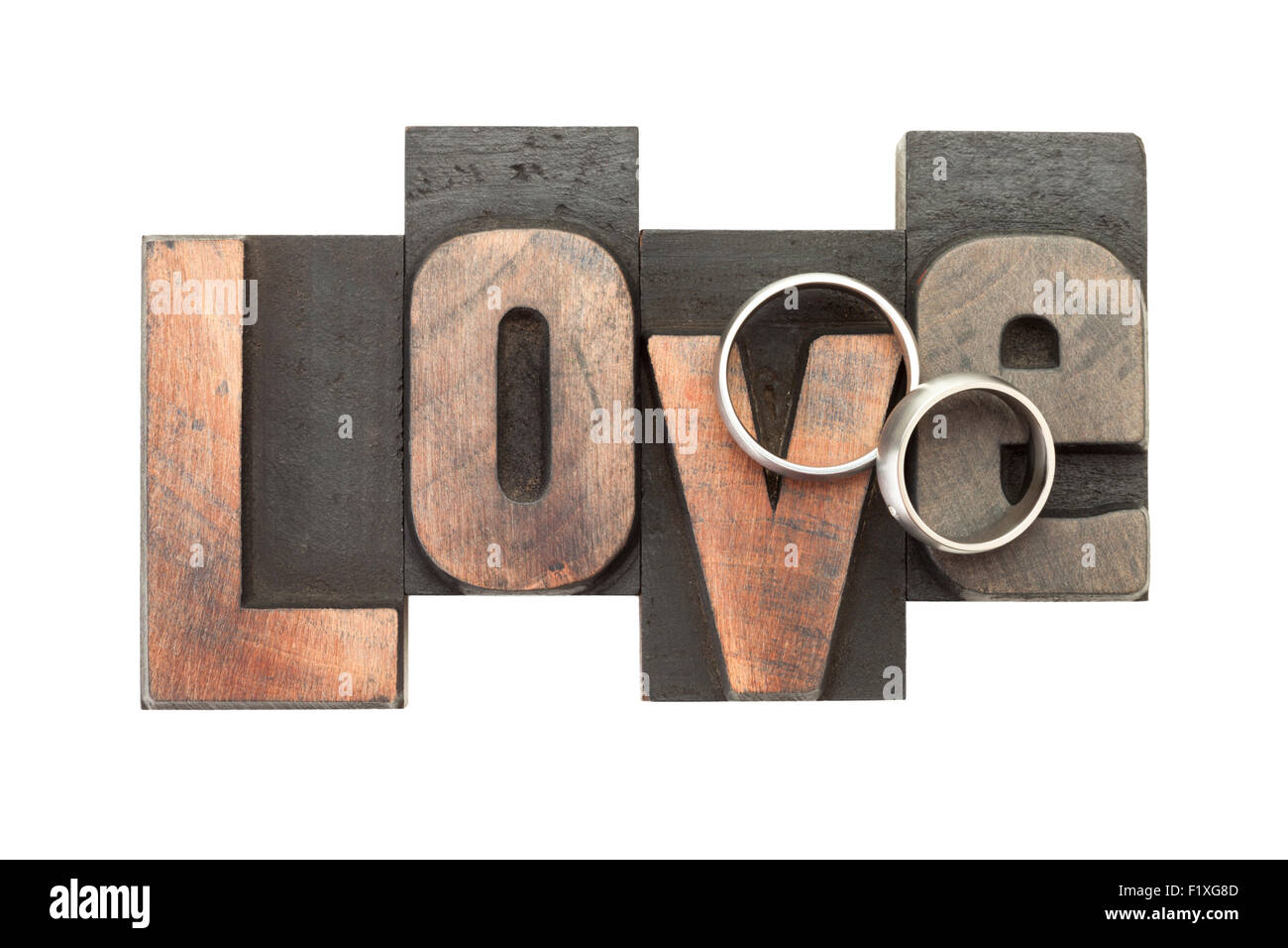 wedding rings upon the word love, written with vintage letterpress printing blocks, isolated on white background - Stock Image