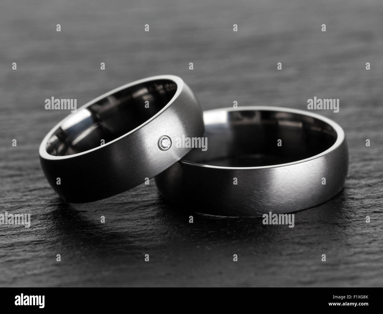 Silver or platinum wedding rings on slate background - Stock Image