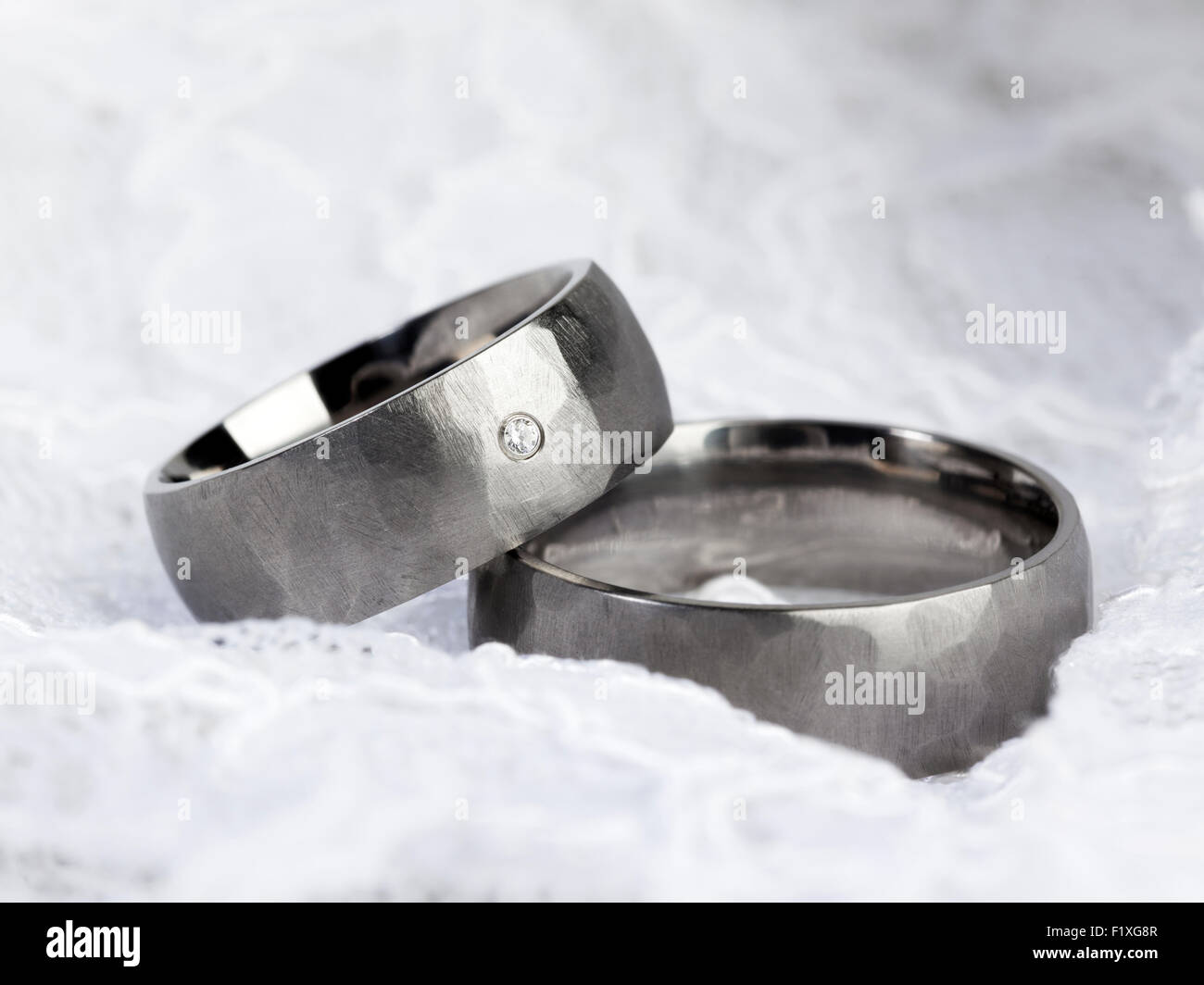 Silver or platinum wedding rings on white lace - Stock Image