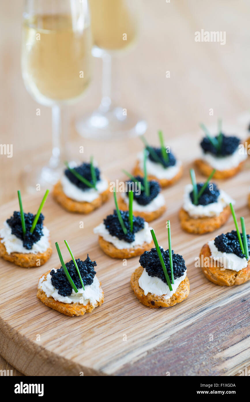 Canapes made from crostini with soft cheese and seaweed 'caviar'. - Stock Image