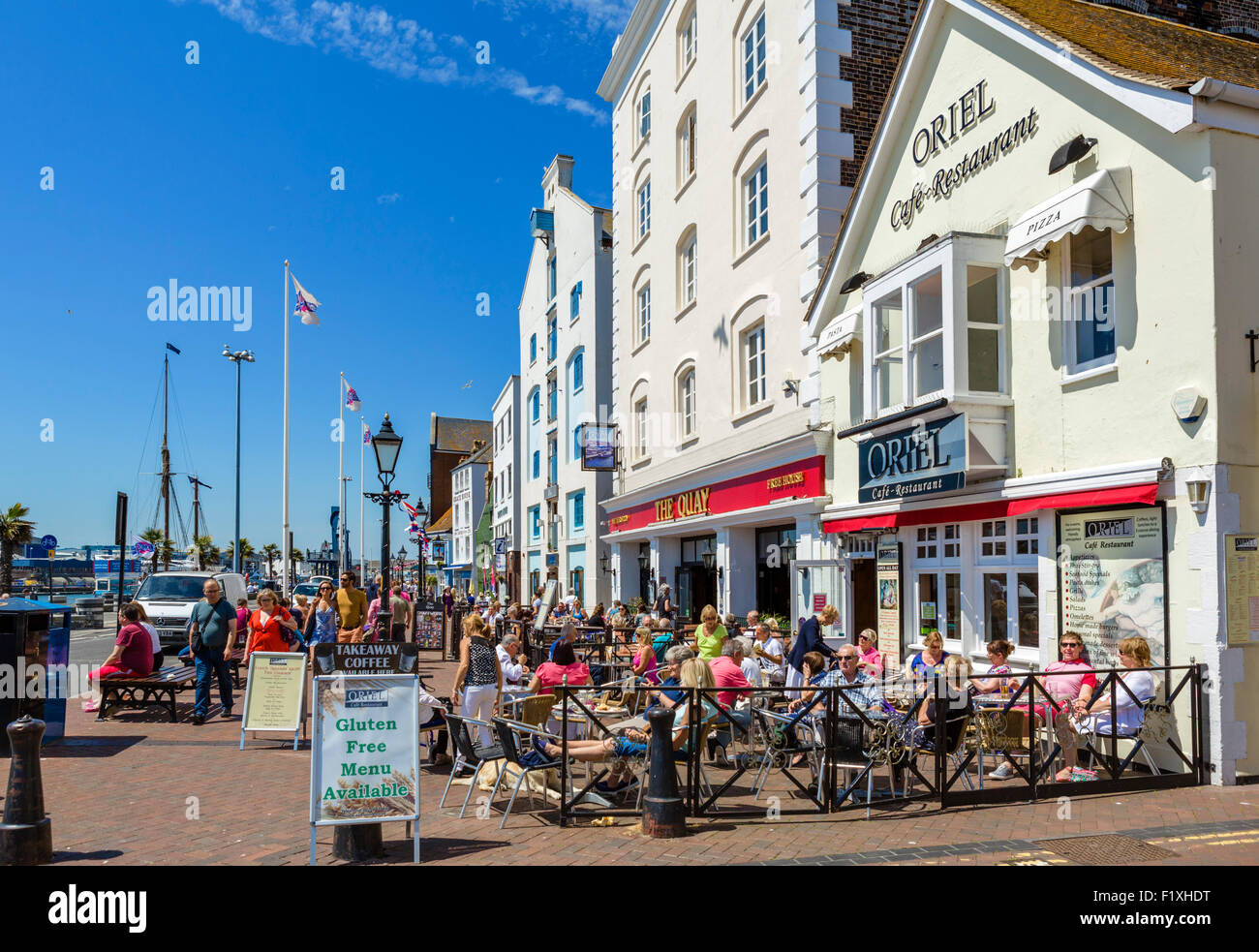People sitting outside The Quay pub and Oriel Cafe on The Quay in Poole, Dorset, England, UK - Stock Image