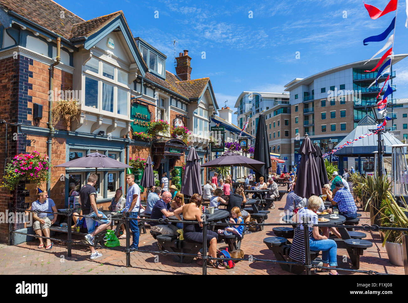 People sitting outside the Jolly Sailor pub on The Quay in Poole, Dorset, England, UK - Stock Image