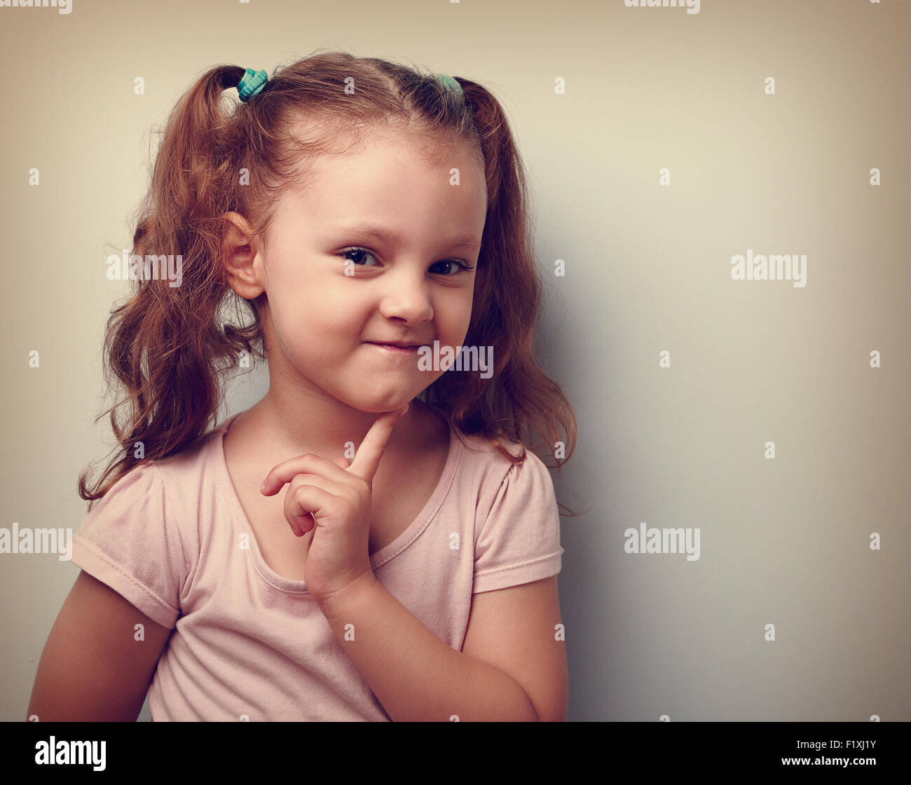 Cunning thinking small kid girl with finger near face looking. Vintage closeup portrait - Stock Image