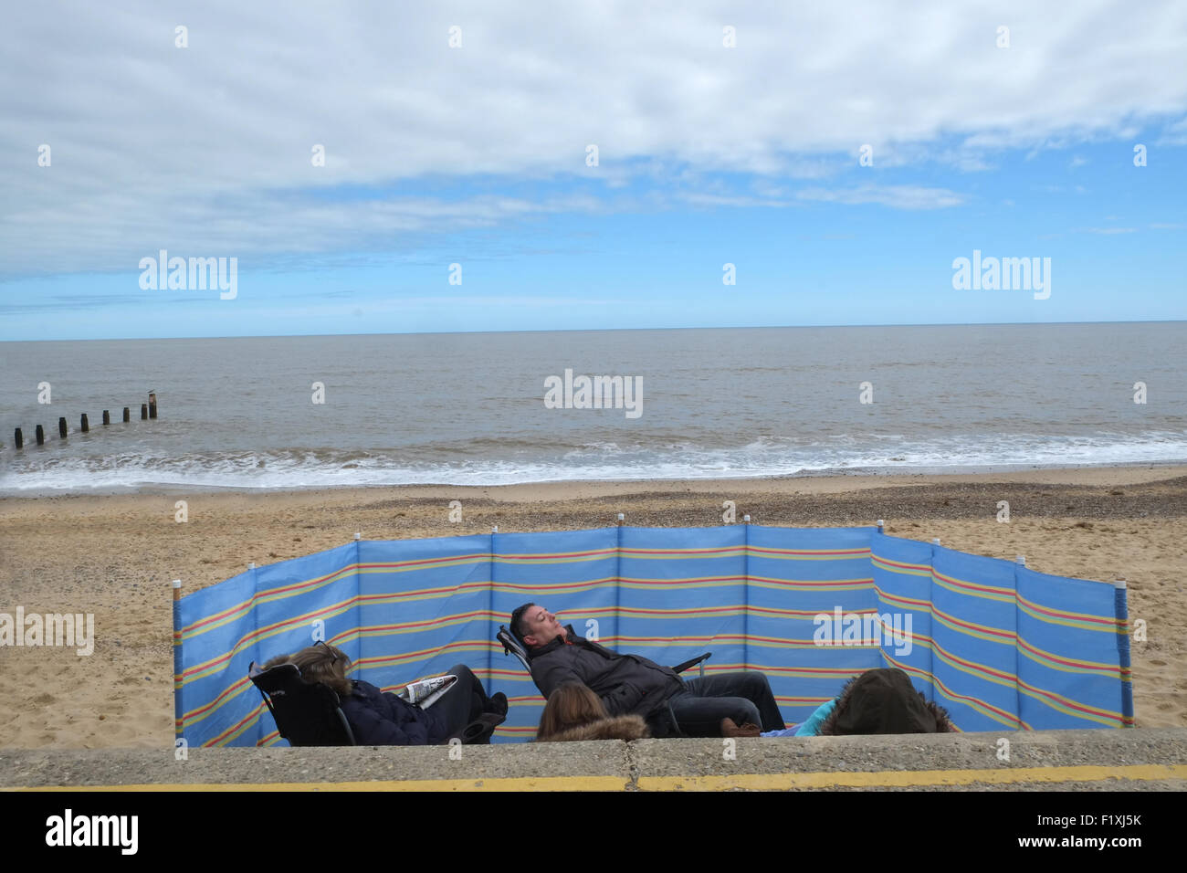 comical day out at the seaside showing family relaxing behind a windbreak - Stock Image