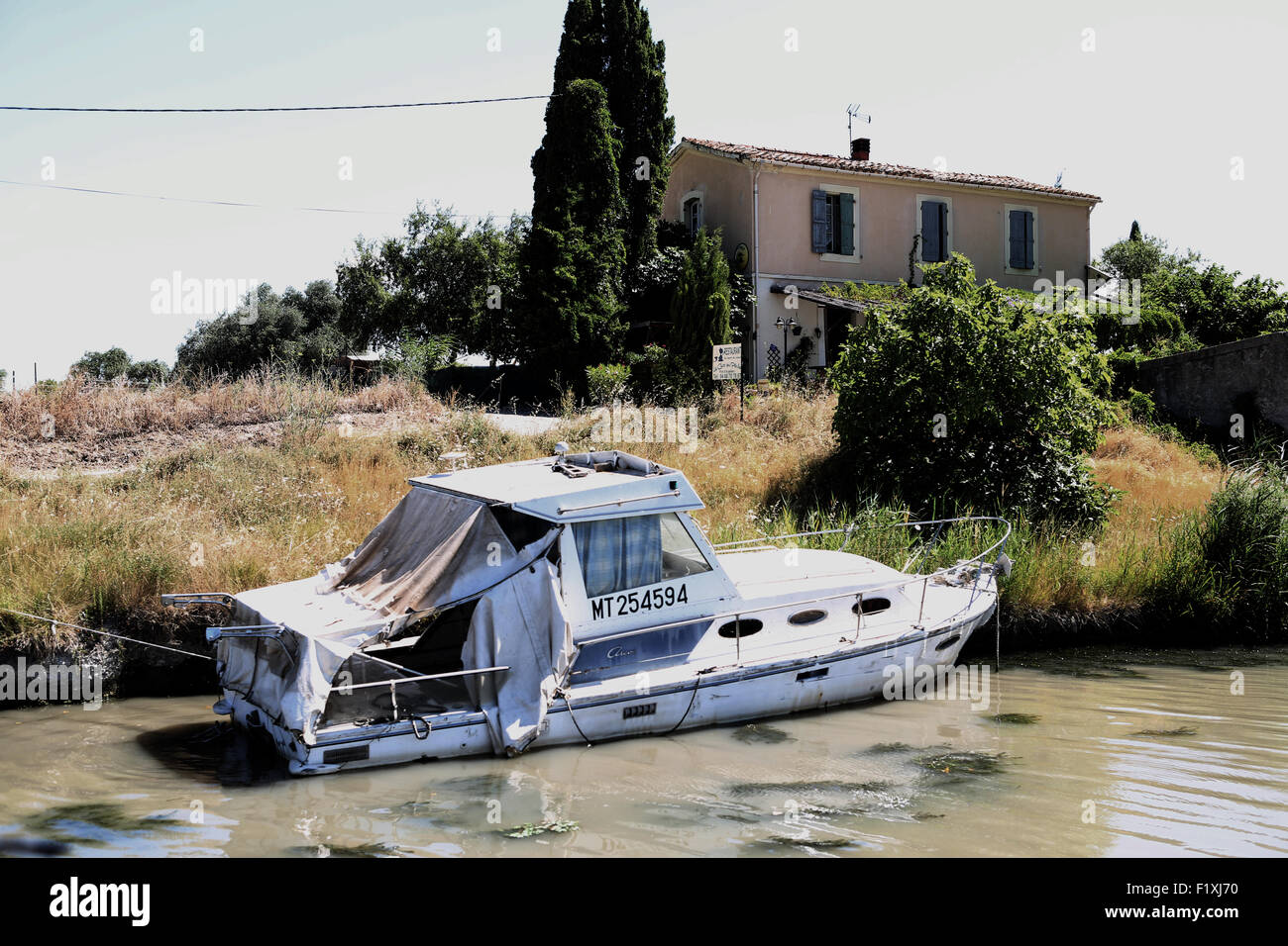 monotone style cruser boat loooking sad and old on a canal near Narbonne in south west france - Stock Image
