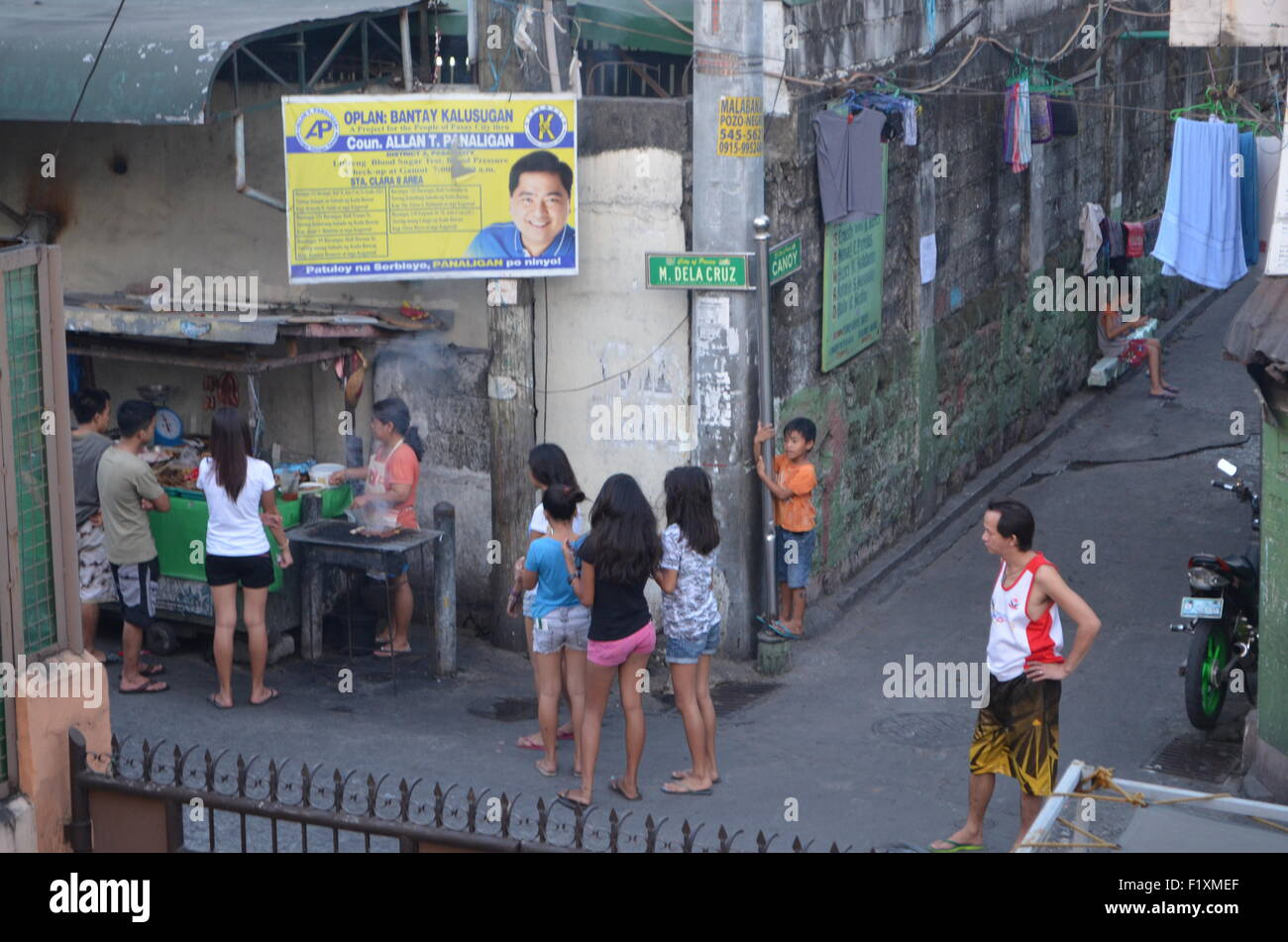 M.Dela Cruz, Manila.A street corner where crowds gather to taste fresh adobo, or fresh chicken, orsausagesbeing - Stock Image
