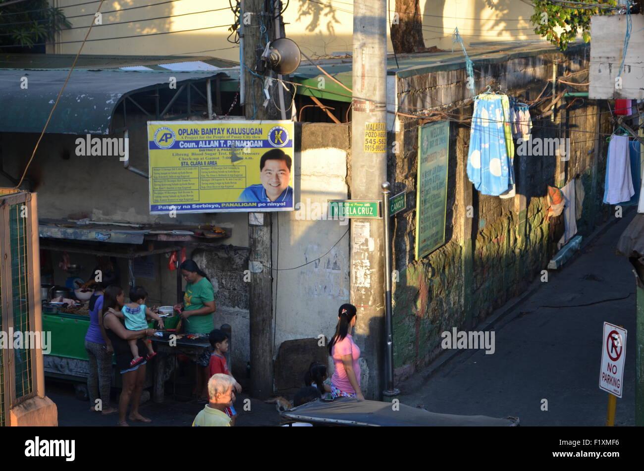 M.Dela Cruz, Manila. A street corner where crowds gather to taste thesausages being warmedup for hem.Abovethemthelocalpolitician - Stock Image