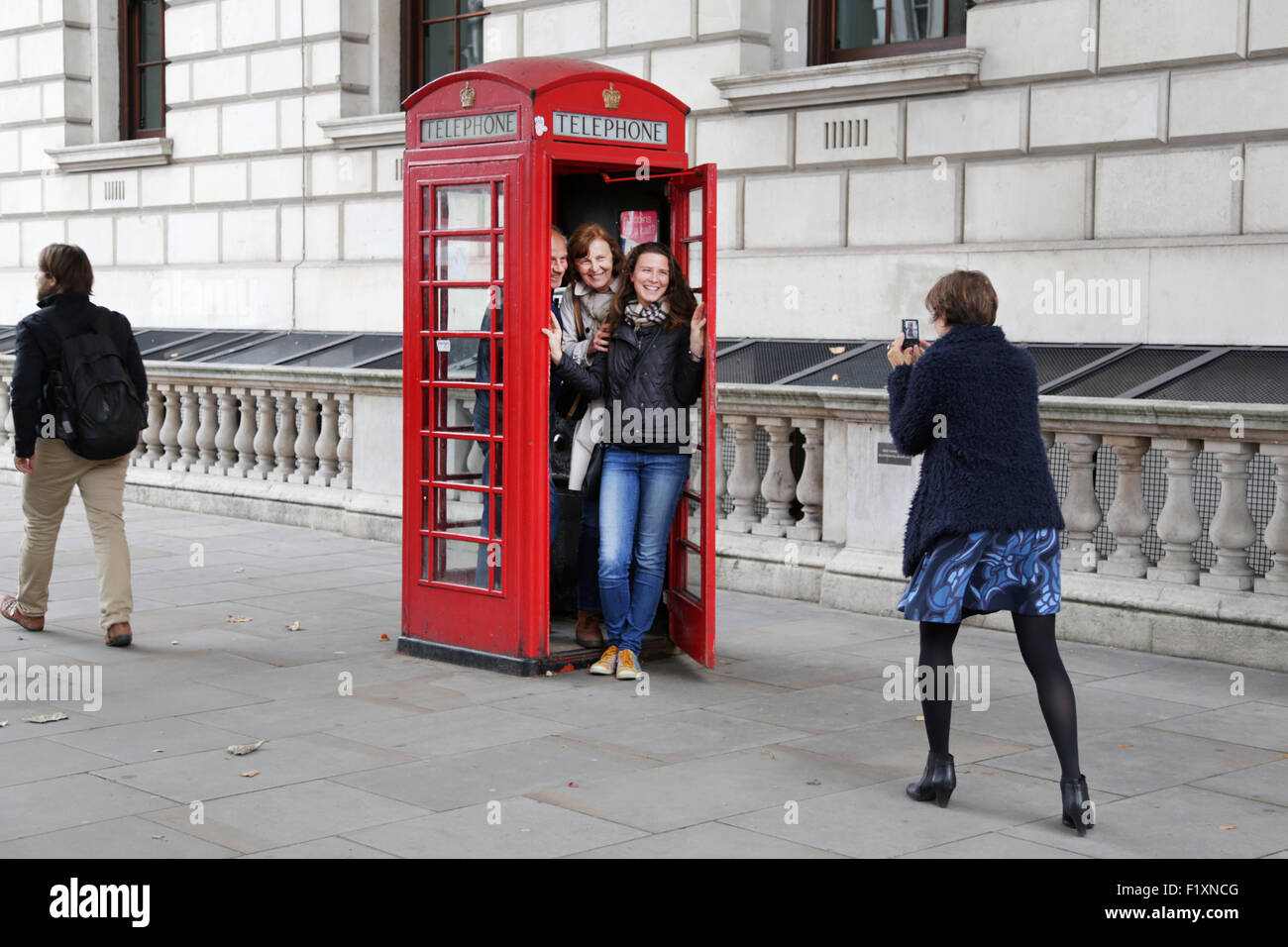 A family group of tourists squeeze into a traditional red English telephone box or kiosk to grab a memorable photo - Stock Image