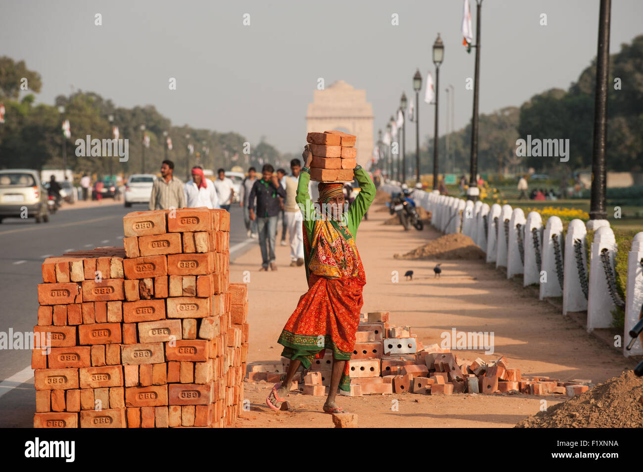 Delhi, India. A woman labourer carrying 8  eight bricks on her head from a pile of bricks at the side of the road - Stock Image