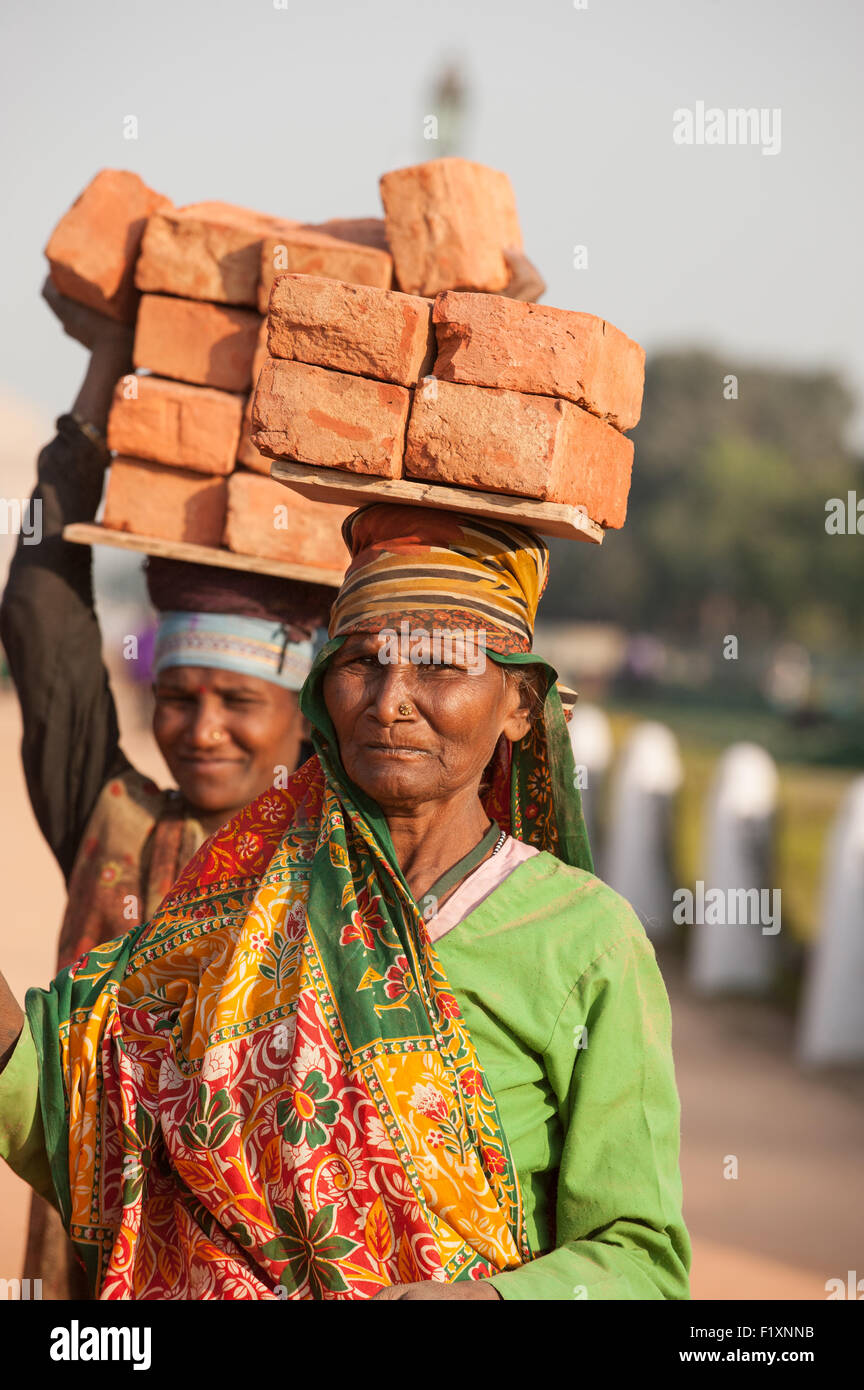Delhi, India. Two women labourers carrying bricks on their heads. - Stock Image