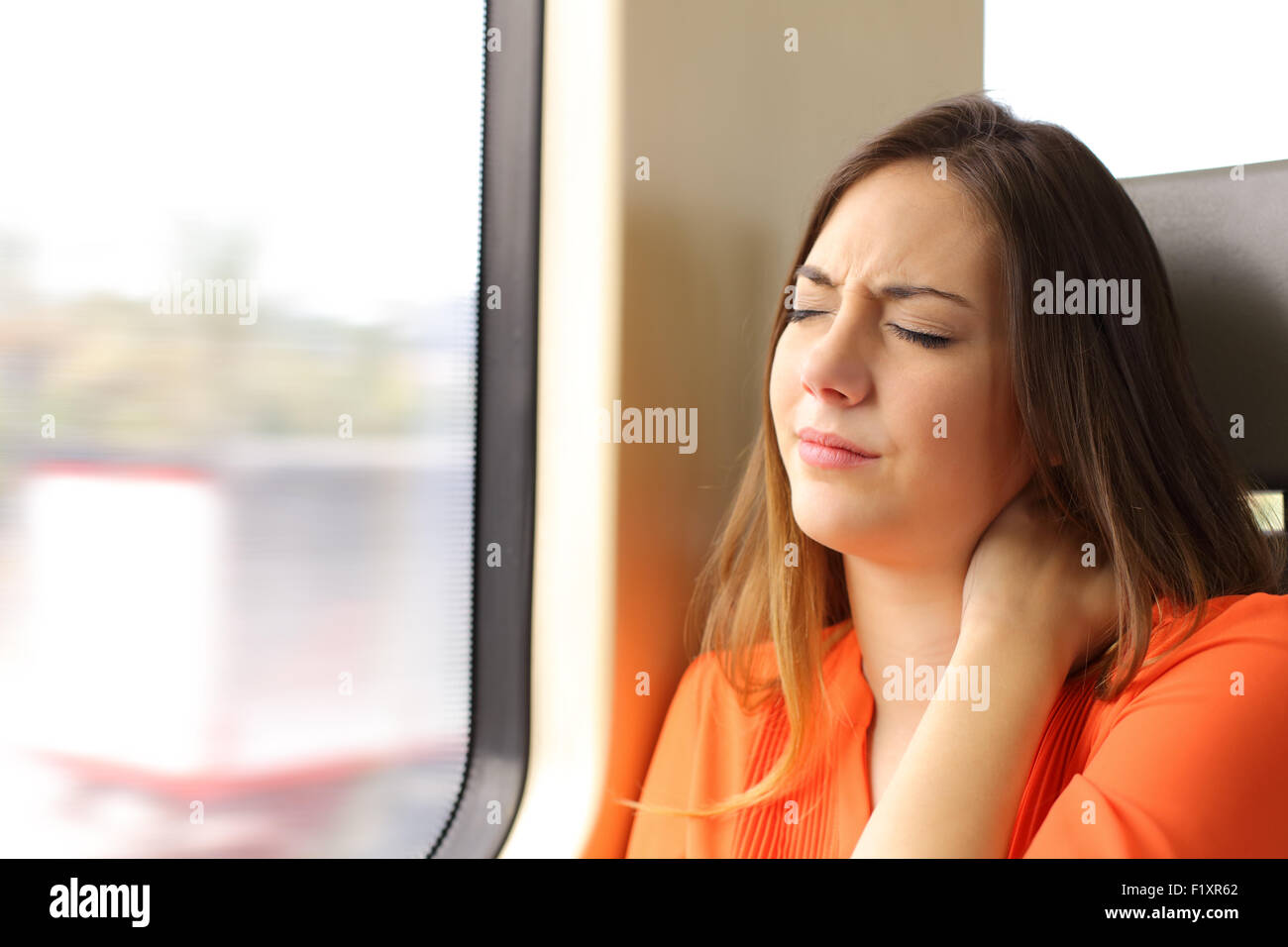 Stressed woman with neck ache sitting in a train wagon complaints - Stock Image