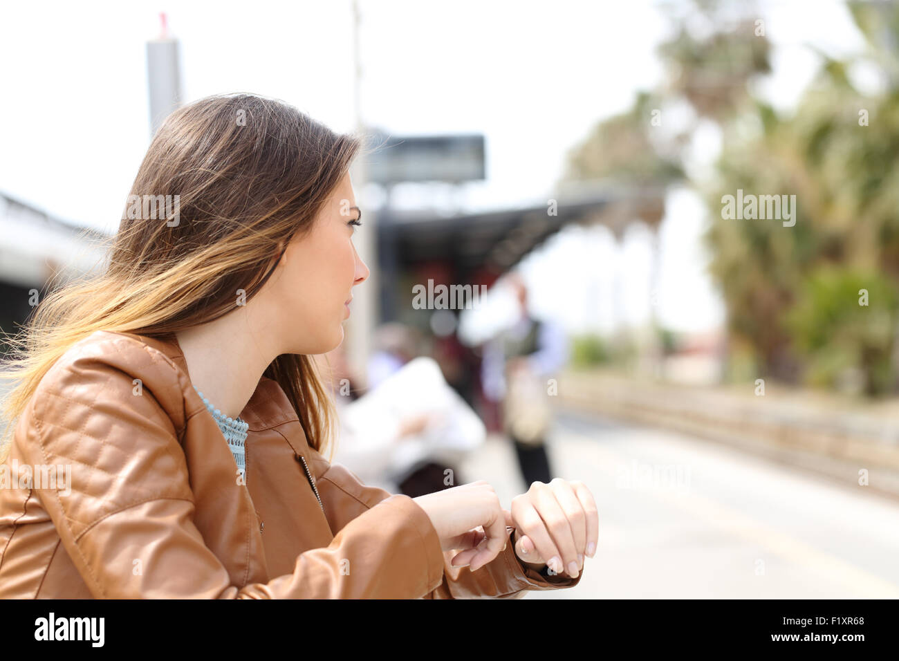Angry girl waiting in a train station and looking to railway - Stock Image