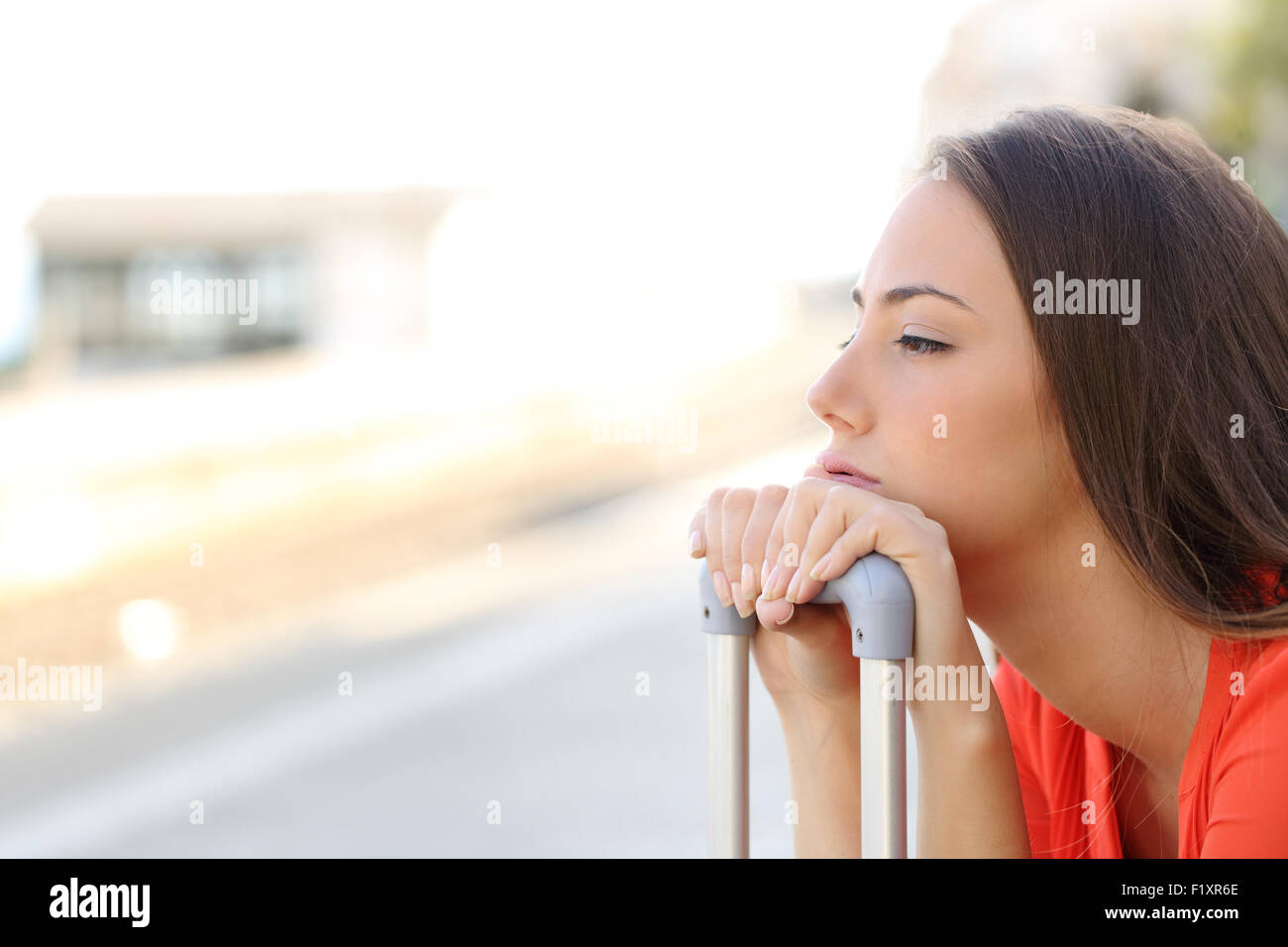 Bored woman waiting for delayed transportation in a train station - Stock Image