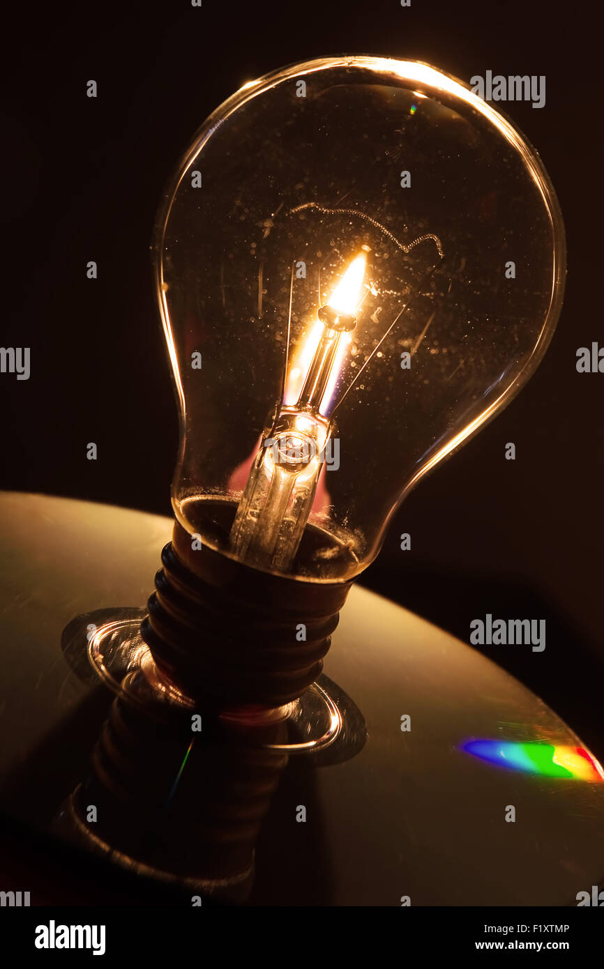 Lightbulb and candle flame - Stock Image