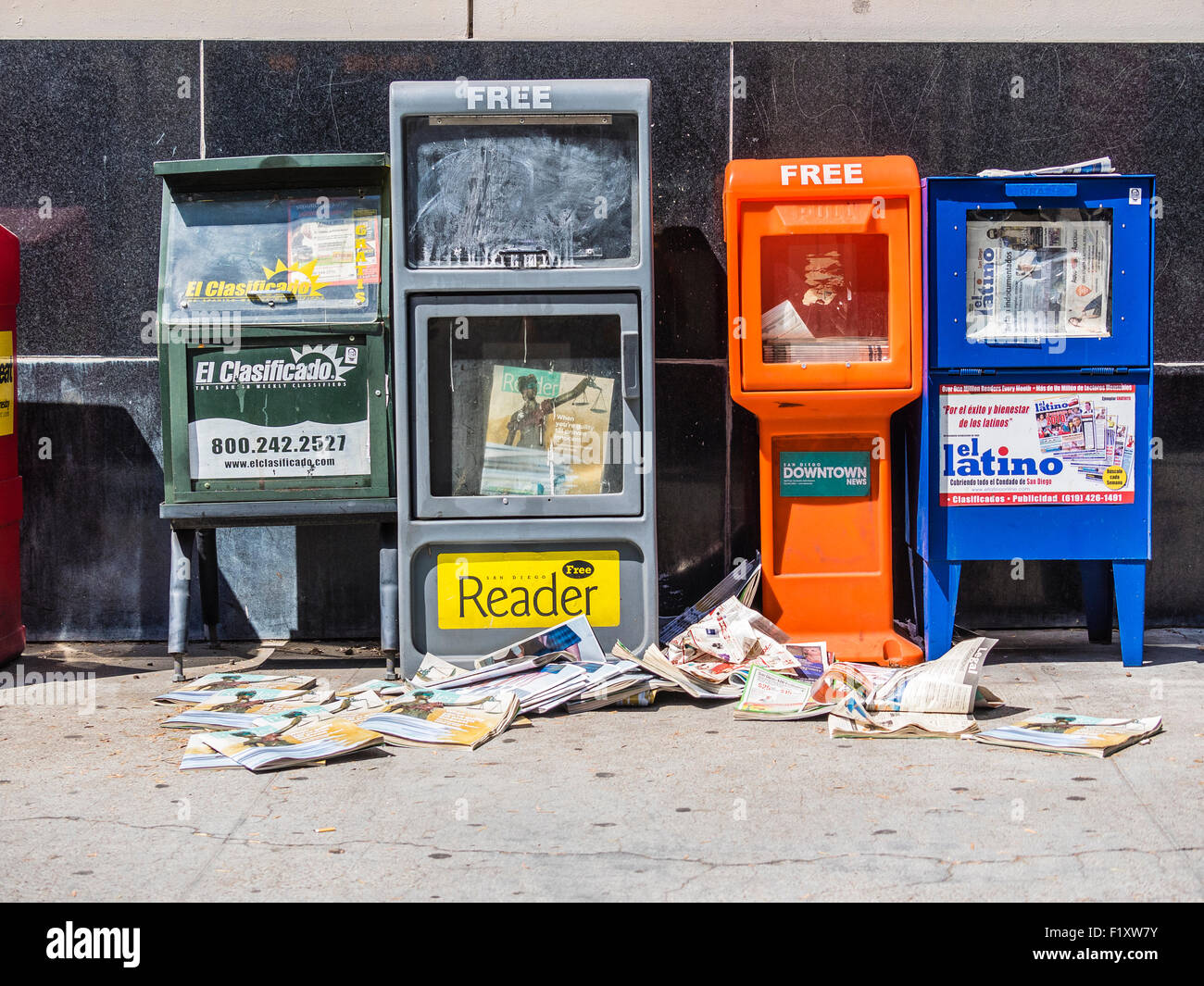 Newspaper stands with loose newspapers lying on the sidewalk creating a mess in San Diego, CA. - Stock Image