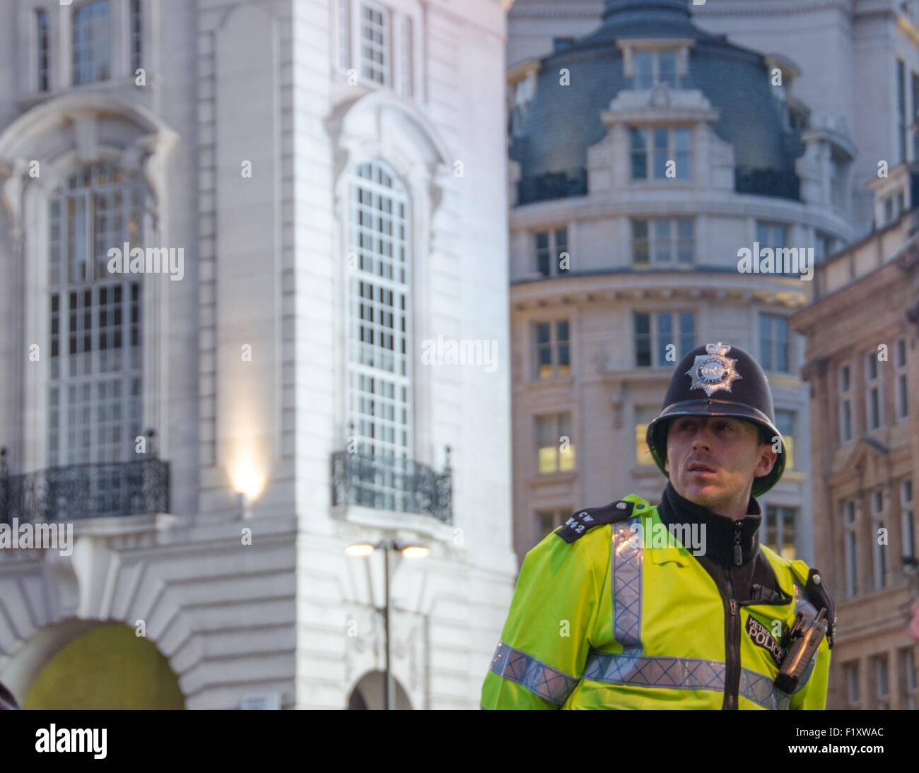 A Metropolitan Police officer surveying the crowds at Piccadilly Circus, London, UK - Stock Image