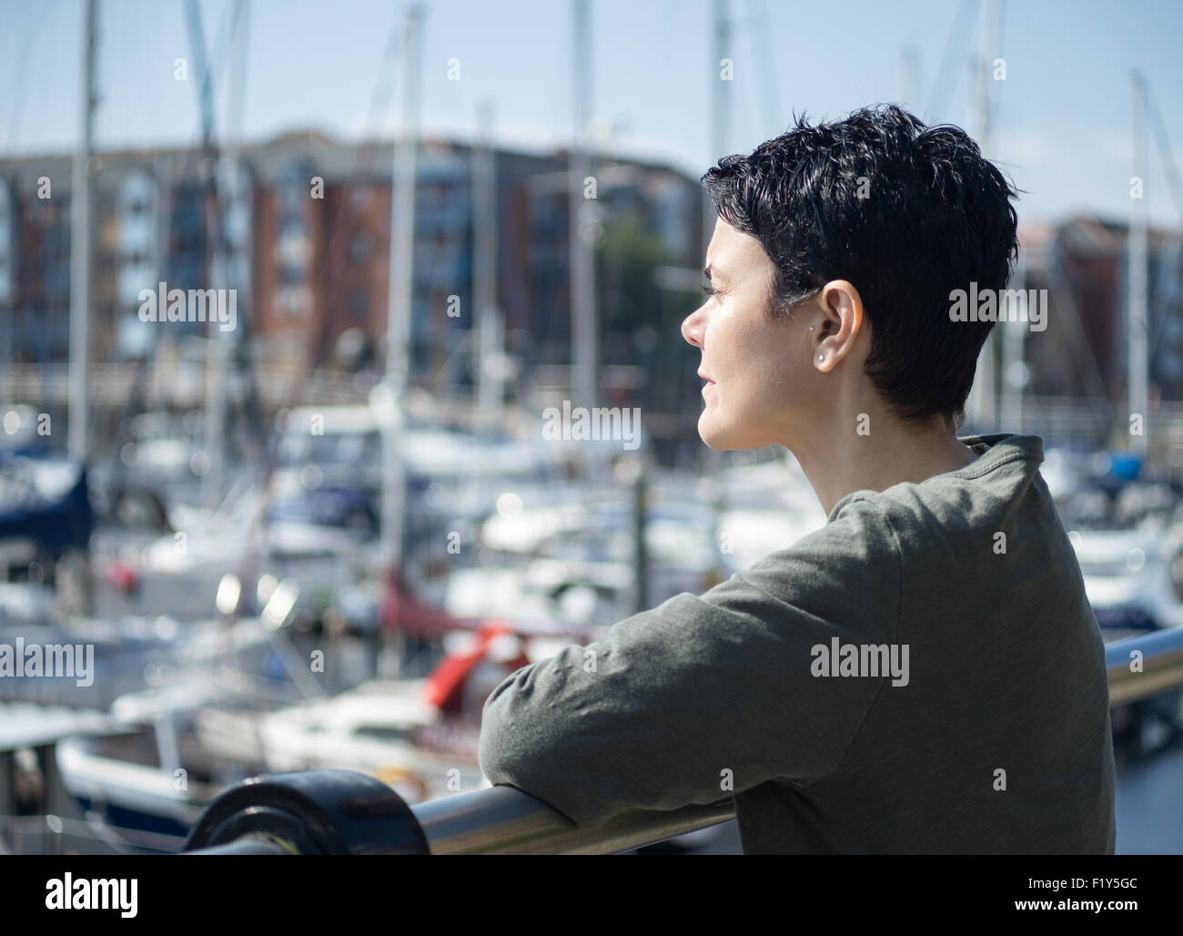 The end of summer.  Female model reminiscing whilst looking out over boats and yachts - Stock Image