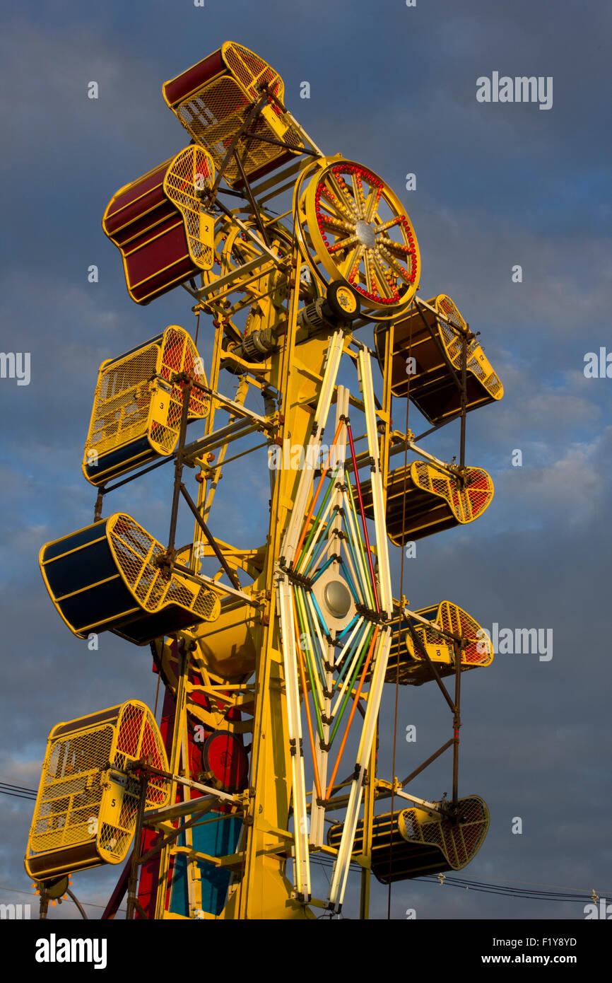 Tacky carnival ride against a threatening sky. - Stock Image