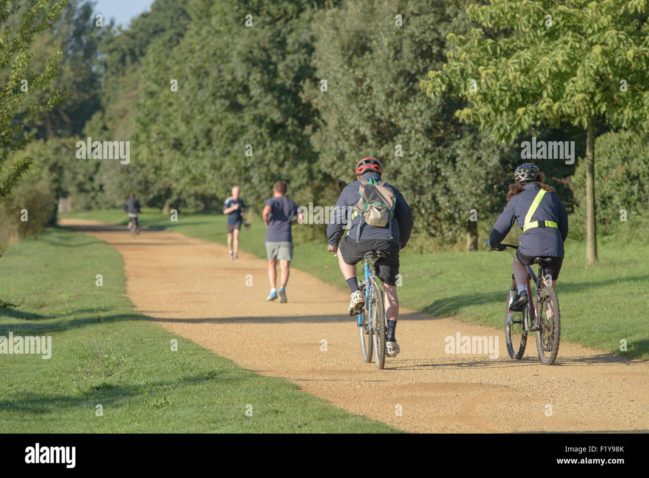 People cycling and jogging along a towpath in London - Stock Image