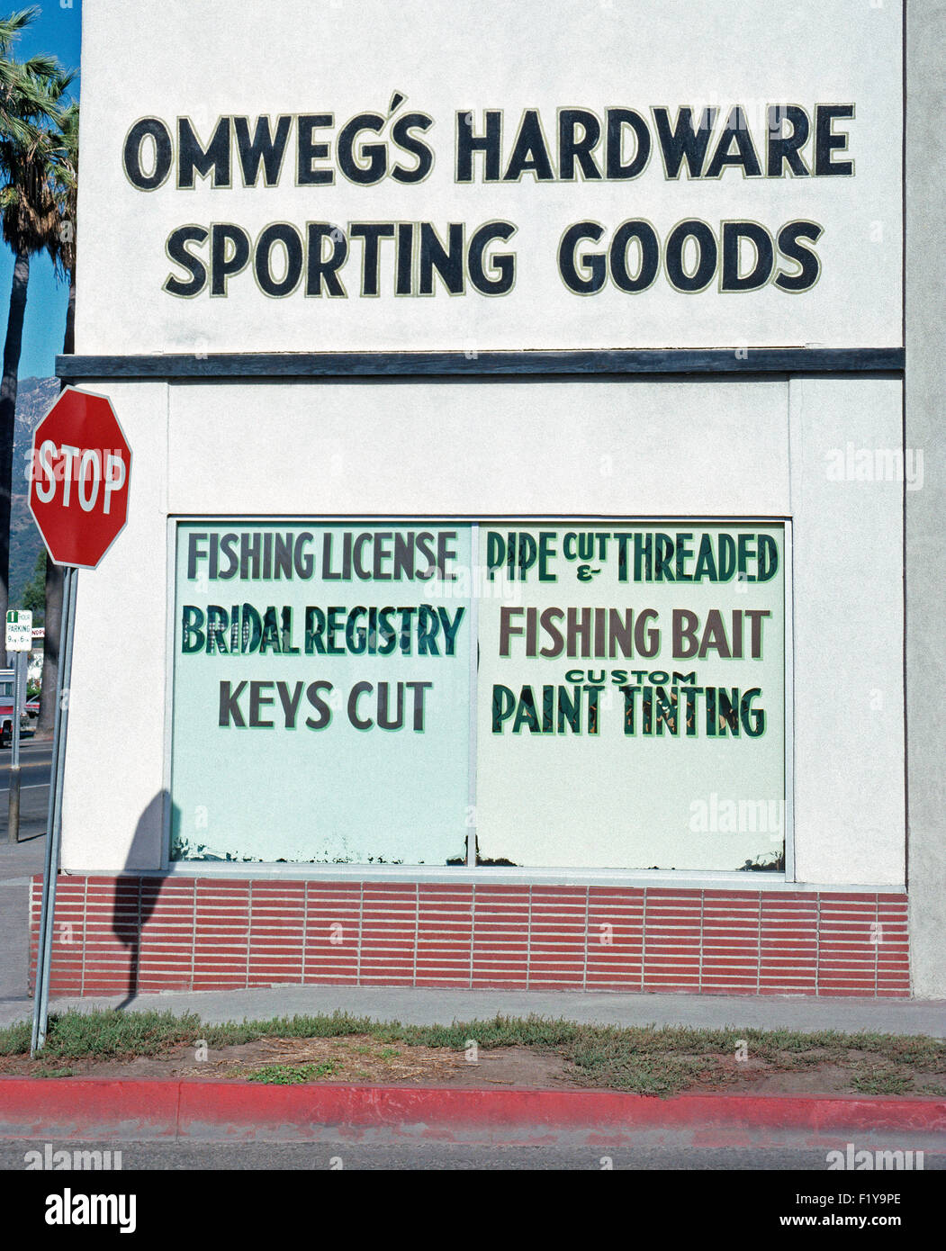 Passersby are surprised to see a Bridal Registry is featured alongside fishing, pipe, paint and key services at - Stock Image