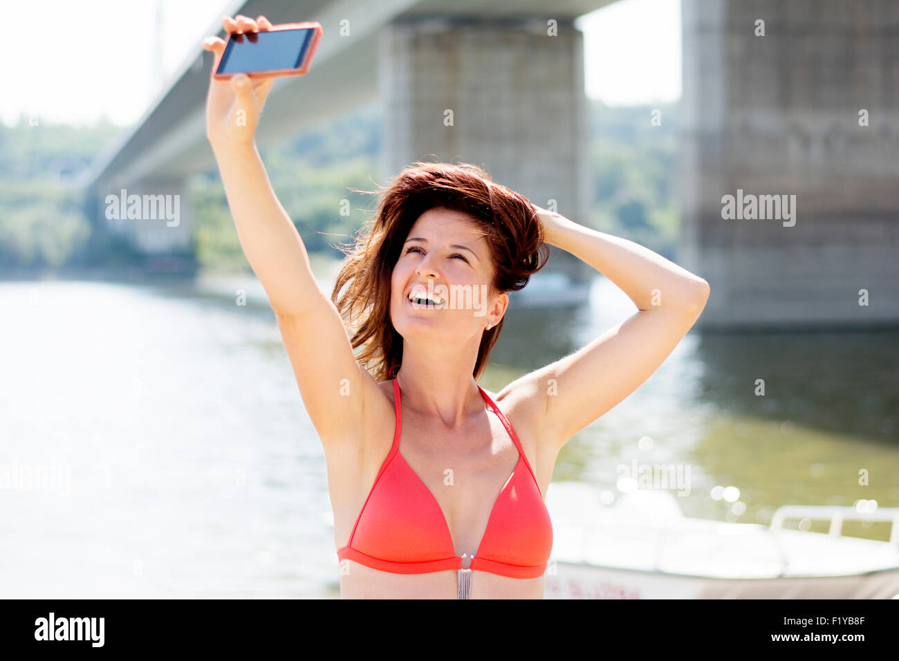 80fe9f31cc Good looking woman wearing red bikini taking self portrait on a beach, she  is feeling relaxed and happy,she is smiling.