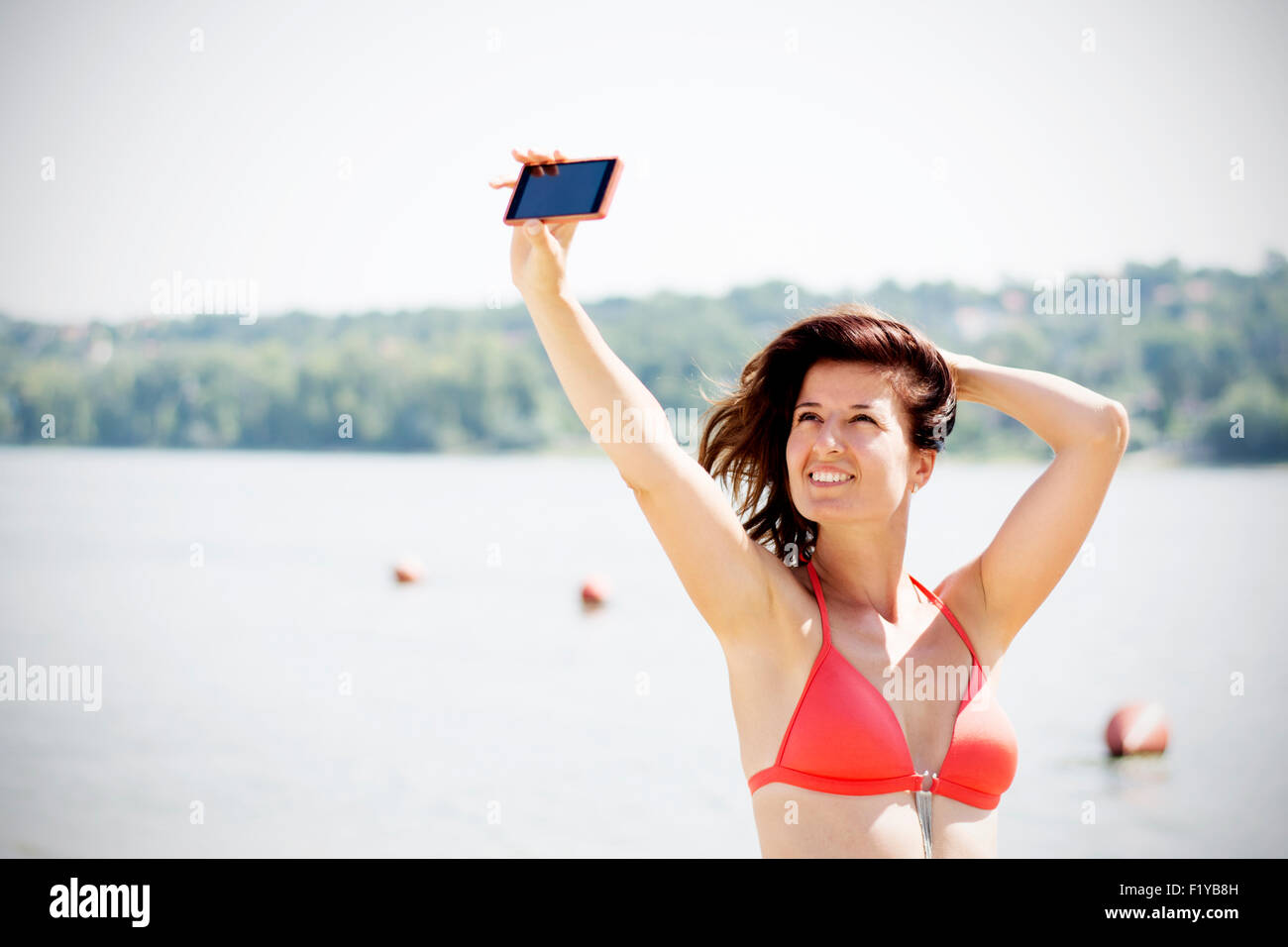 f48e944e24 Attractive young brunette woman taking self portrait with her phone on beach.  She is wearing