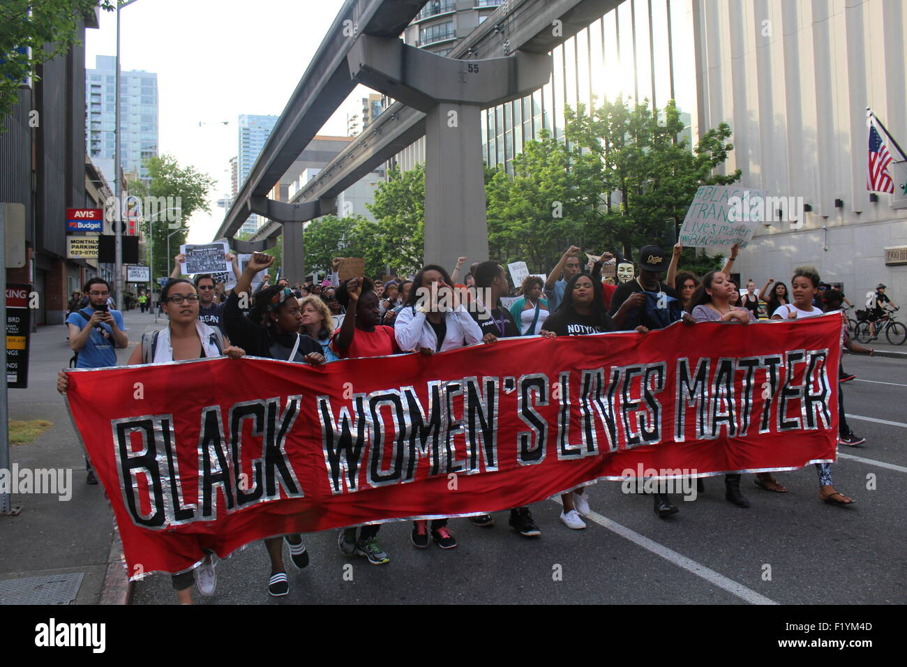 Members of the black lives matter movement carry a gender specific banner while marching down 5th ave in downtown - Stock Image