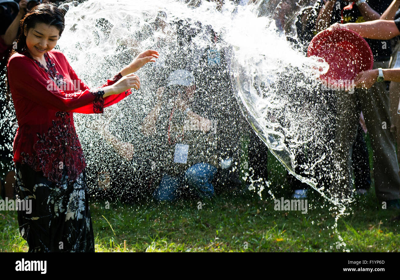 Young Asian models splashed with water. - Stock Image