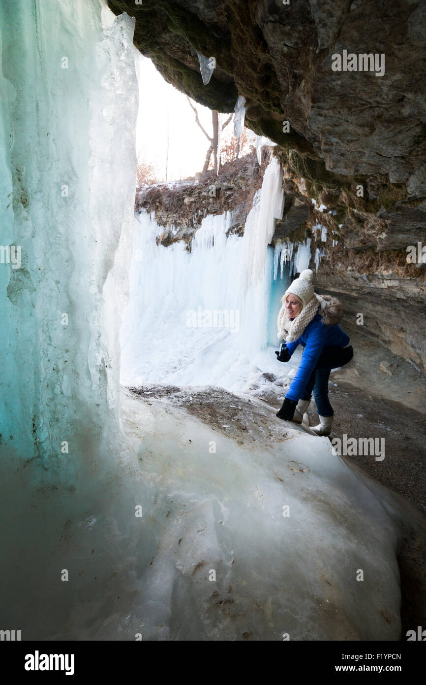 Caucasian woman in winter clothing explores behind frozen Minnehaha Falls in winter, Minneapolis, MN, USA - Stock Image