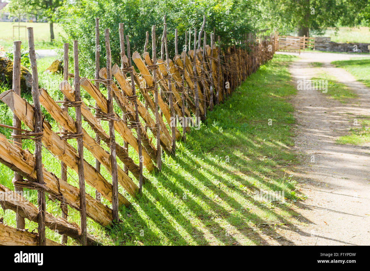 Wicker Fence Or Lath Near Country Road On Sunny Day Stock Photo