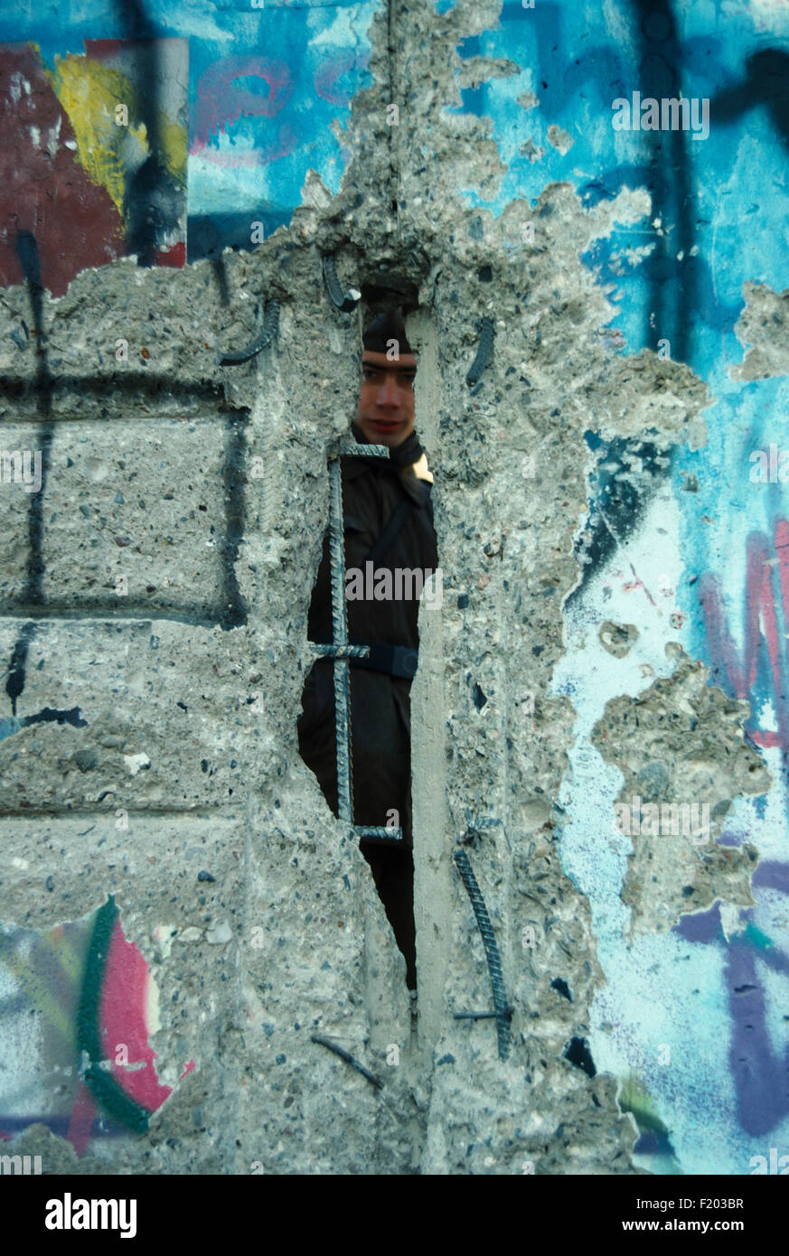 Germany Berlin, East German border guard looking through crack in the Wall in 1989. - Stock Image