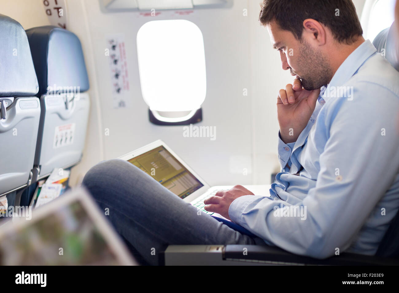 Businessman working with laptop on airplane. - Stock Image