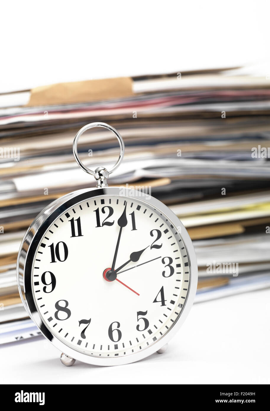 Alarm clock with office files in the background - Stock Image
