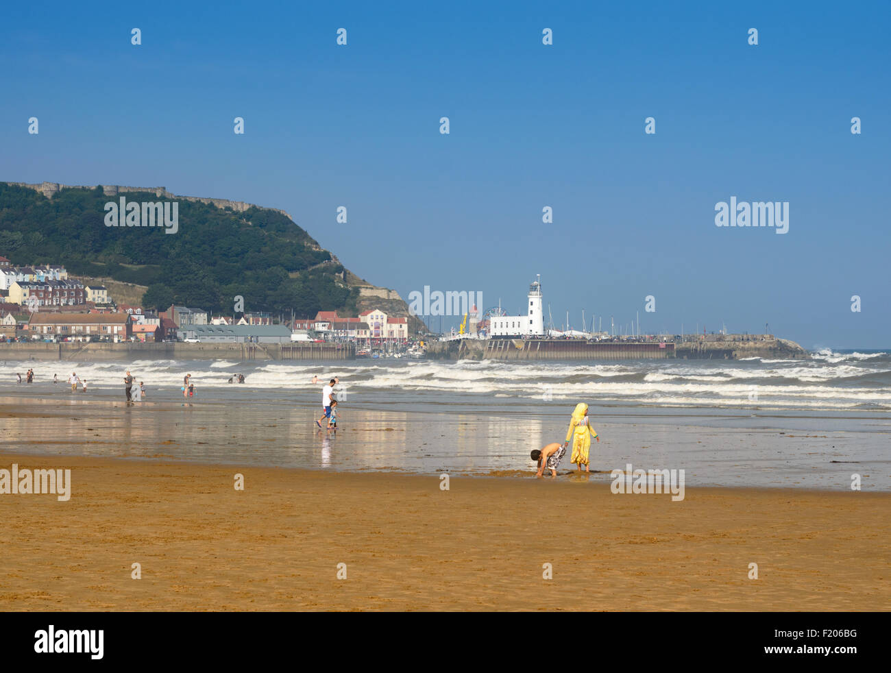A woman (assumed to be Muslim) on beach with young girl. In Scarborough, England. - Stock Image
