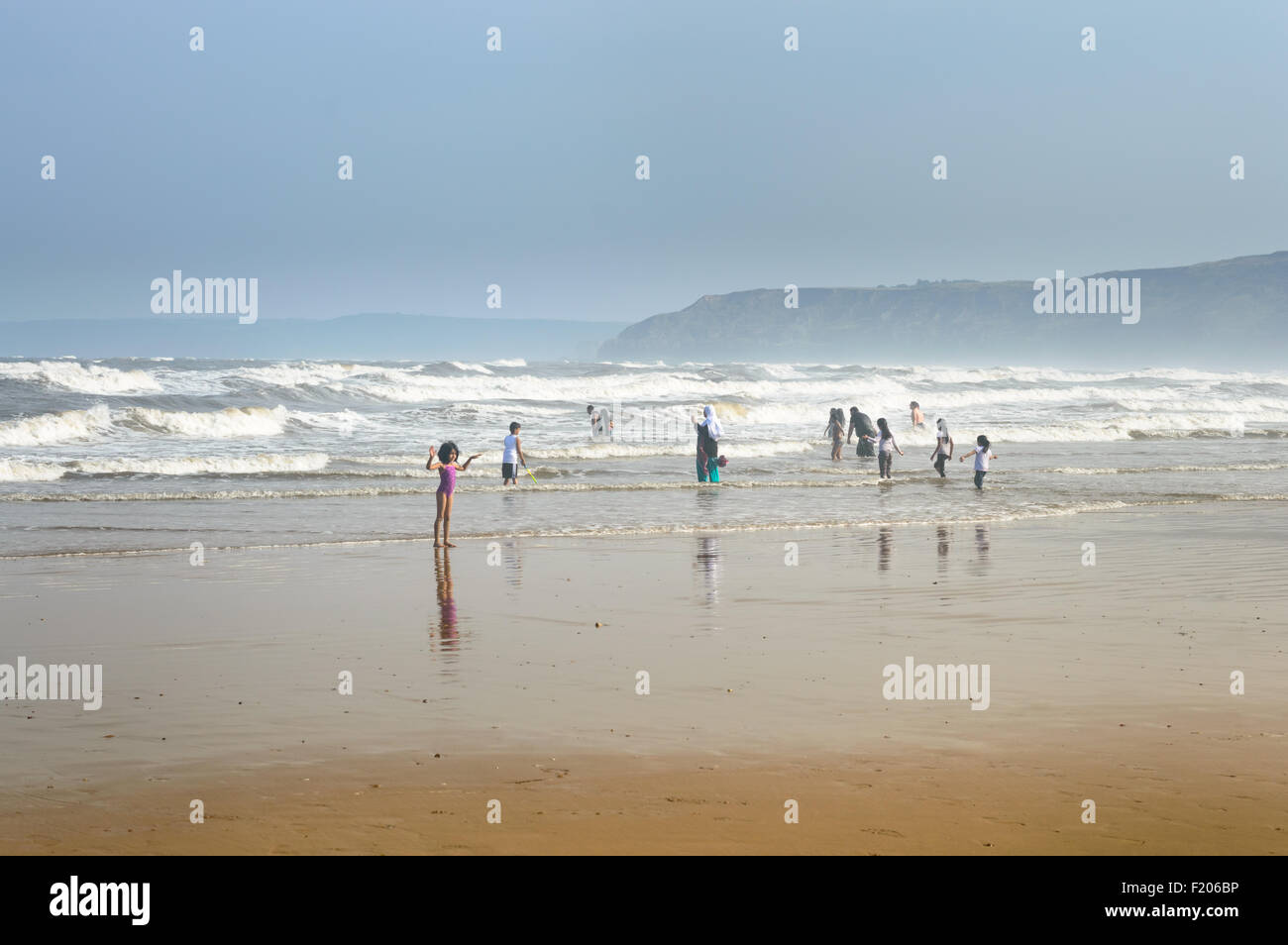 A family (assumed to be Muslim) wading in the sea on Scarborough beach. In Scarborough, Englan - Stock Image