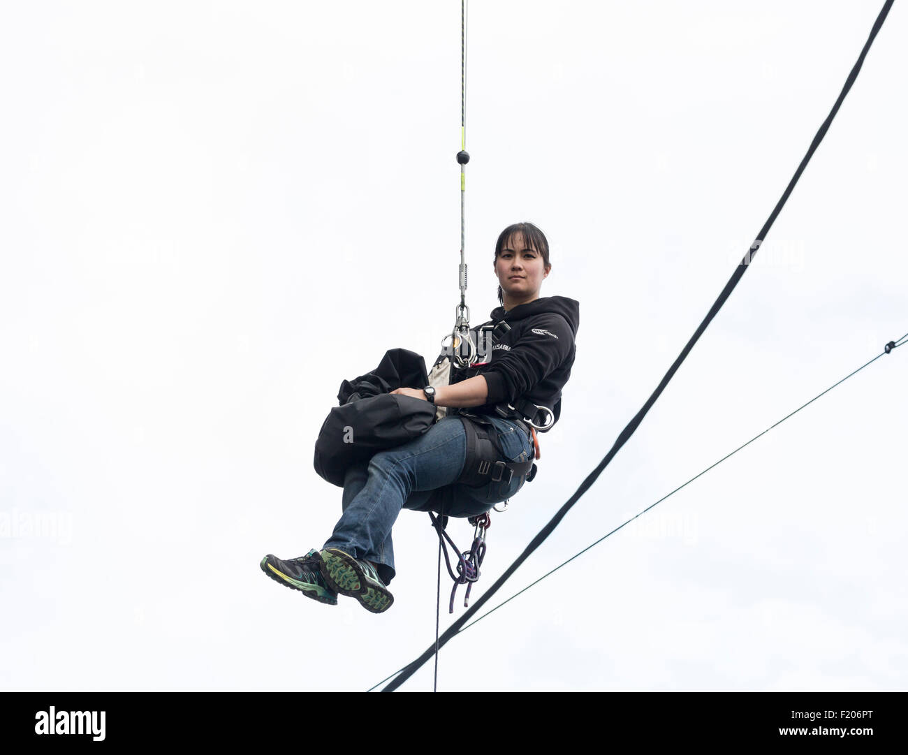 Young woman with a calm expression hangs dangling from a rope in a harness with safety equipment Stock Photo