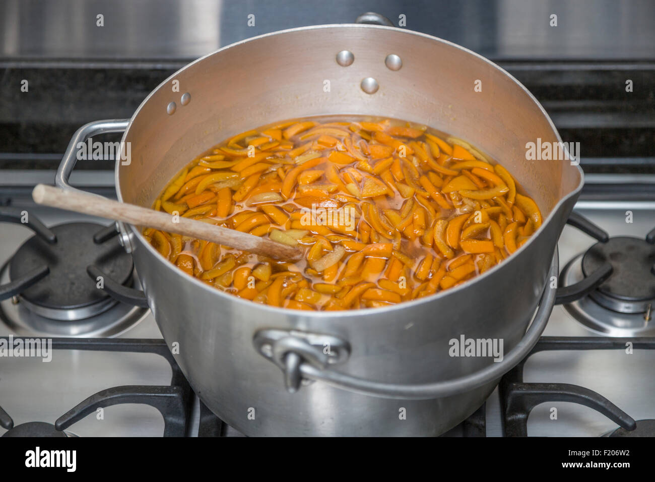 Sliced peeled oranges heating in a metal preserving pan on a gas hob in preparation for boiling to make home-made - Stock Image