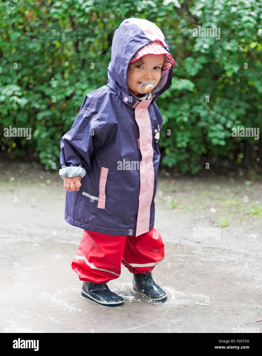 Kind mit Regenkleidung in einer Pfütze - Stock Image