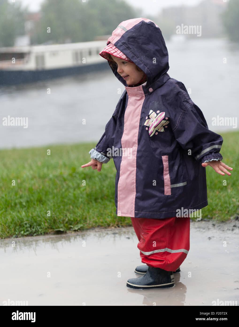 Kleinkind steht bei Regen in einer Pfütze - Stock Image