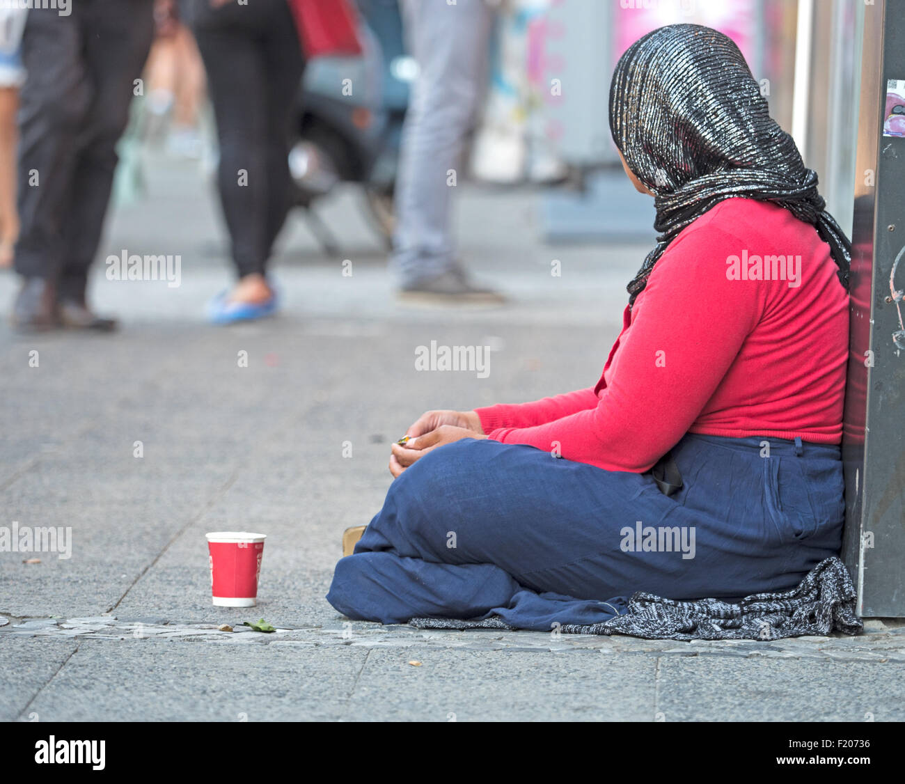 Bettlerin sitzt auf der Straße - Stock Image