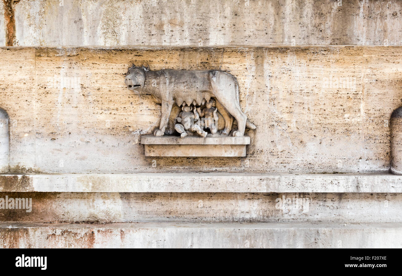 Romulus and Remus suckling on a wolf, a relief on the base of a fountain in Piazza del VIiminale, Rome, Italy - Stock Image