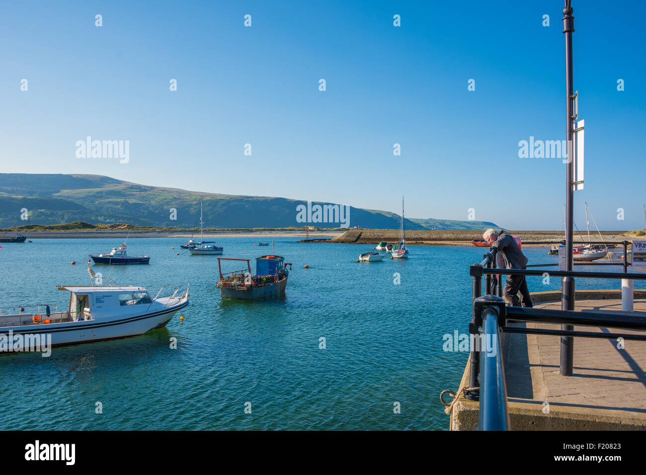 A man looking into the Harbour from the quayside at barmouth gwynedd Wales UK Stock Photo