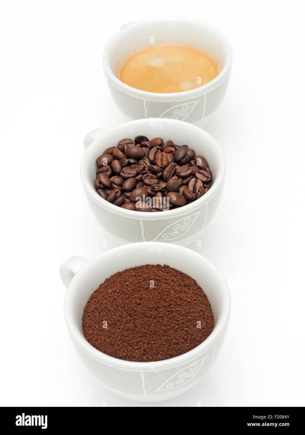 3 Kaffeetassen mit Kaffeepulver, Kaffeebohnen und Kaffee - Stock Image