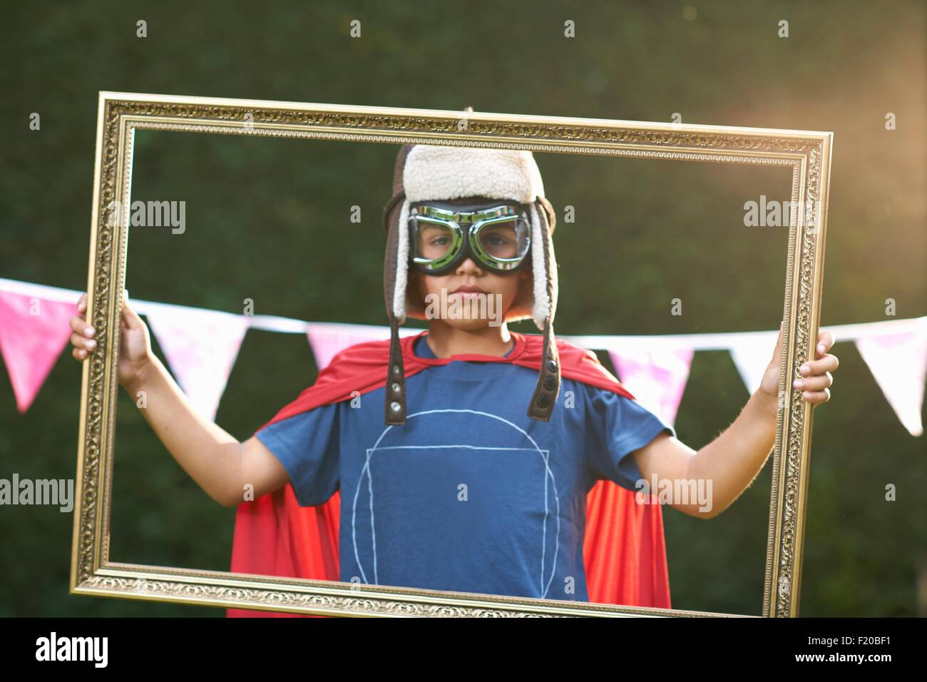 Portrait of boy looking through picture frame wearing cape, goggles and flying hat - Stock Image