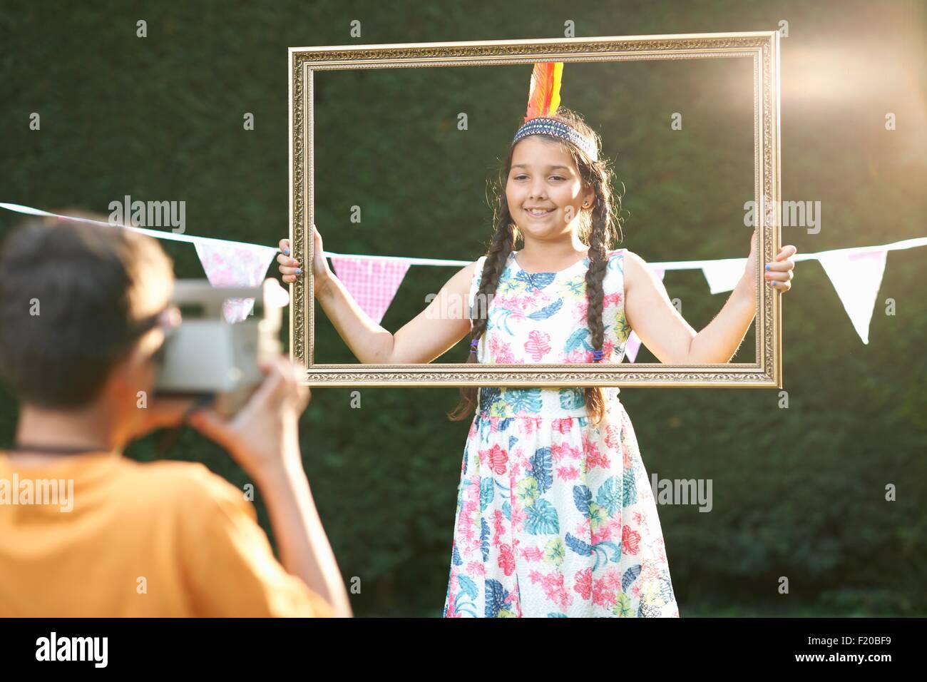 Girl looking through picture frame, having photograph taken - Stock Image