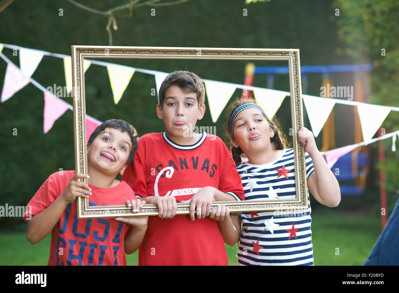 Three children looking through picture frame, sticking out tongues - Stock Image
