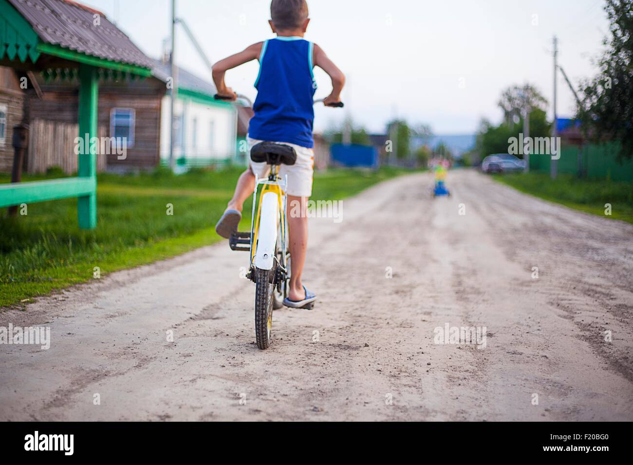 Young boy, riding bicycle along dirt road, rear view - Stock Image