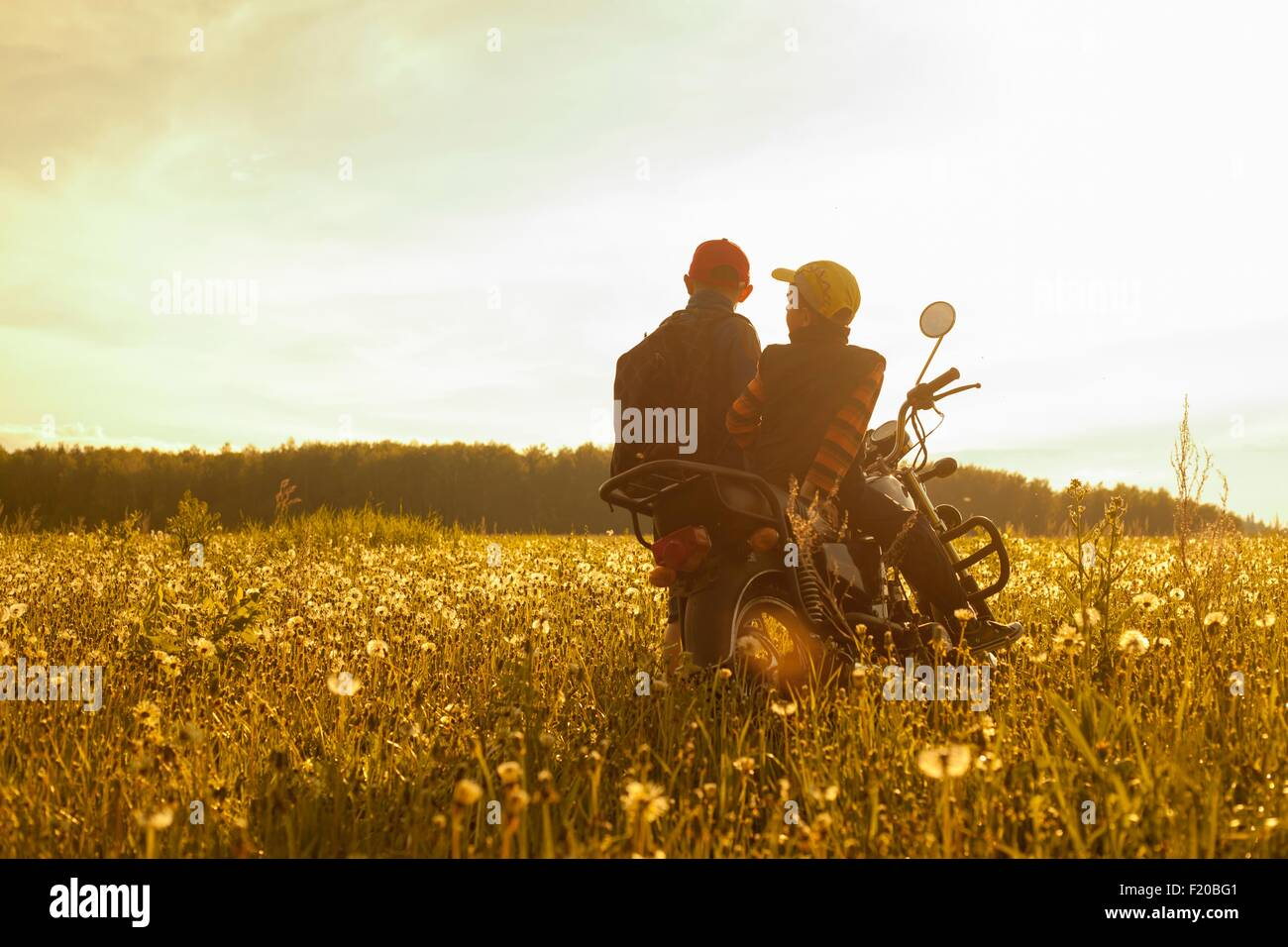 Two young boys, sitting on motorbike, in field, rear view - Stock Image