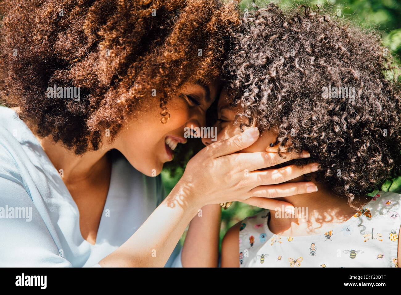 Close up side view of mother and daughter nose to nose - Stock Image