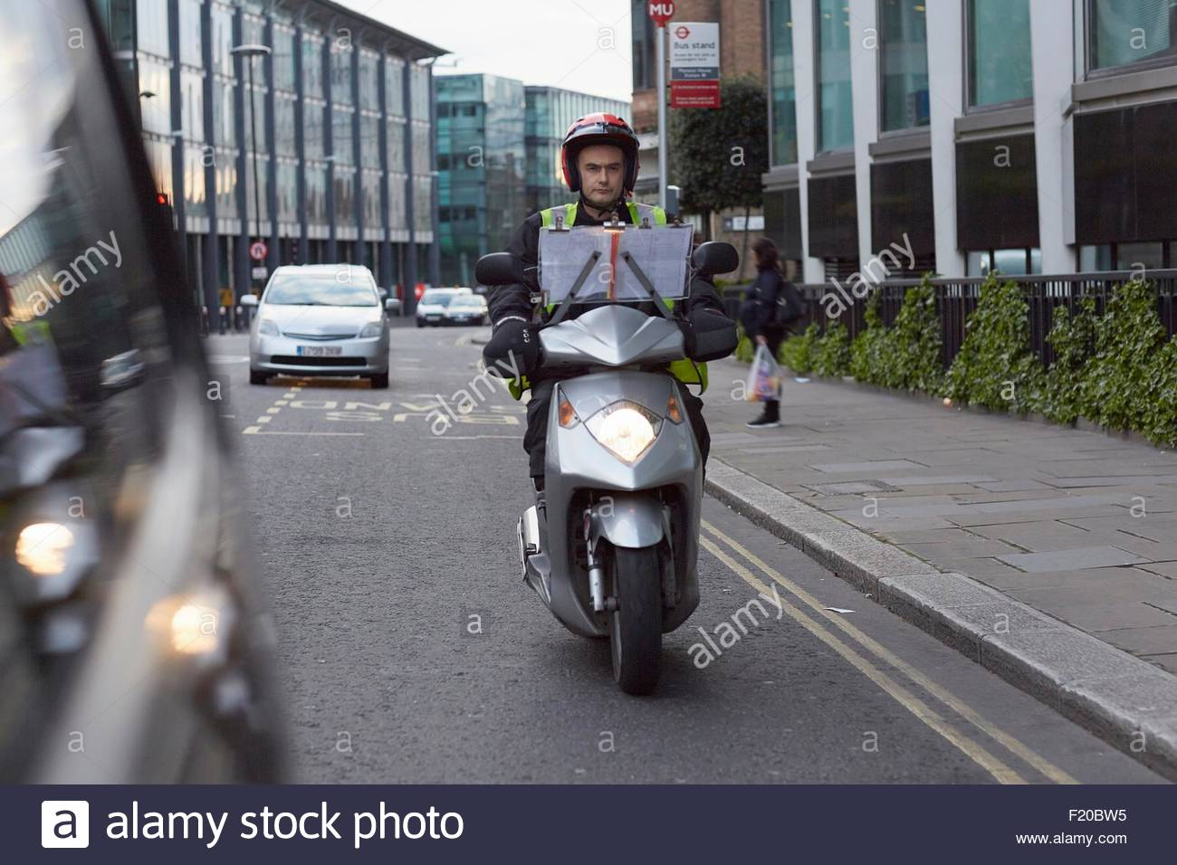 Motor scooter rider, undertaking taxi driver training 'the knowledge', on the move in London - Stock Image
